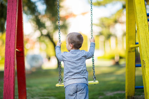 Blond boy swinging on the playground,rear