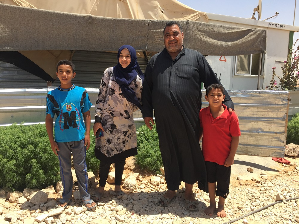 Abu Kareem with three of his four children outside their home in Za'atari refugee