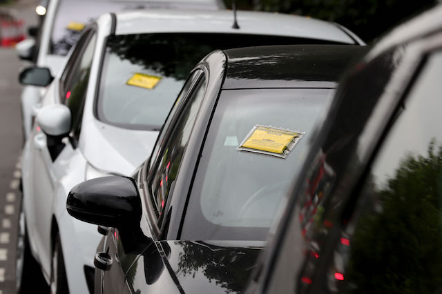 Penalty charge notices affixed to several cars left in restricted parking bays on a road near Gatwick Airport, as dozens of people have flown back to the airport to find difficulty being reunited with their cars after meet-and-greet parking company Gatwick First Parking apparently stopped trading.