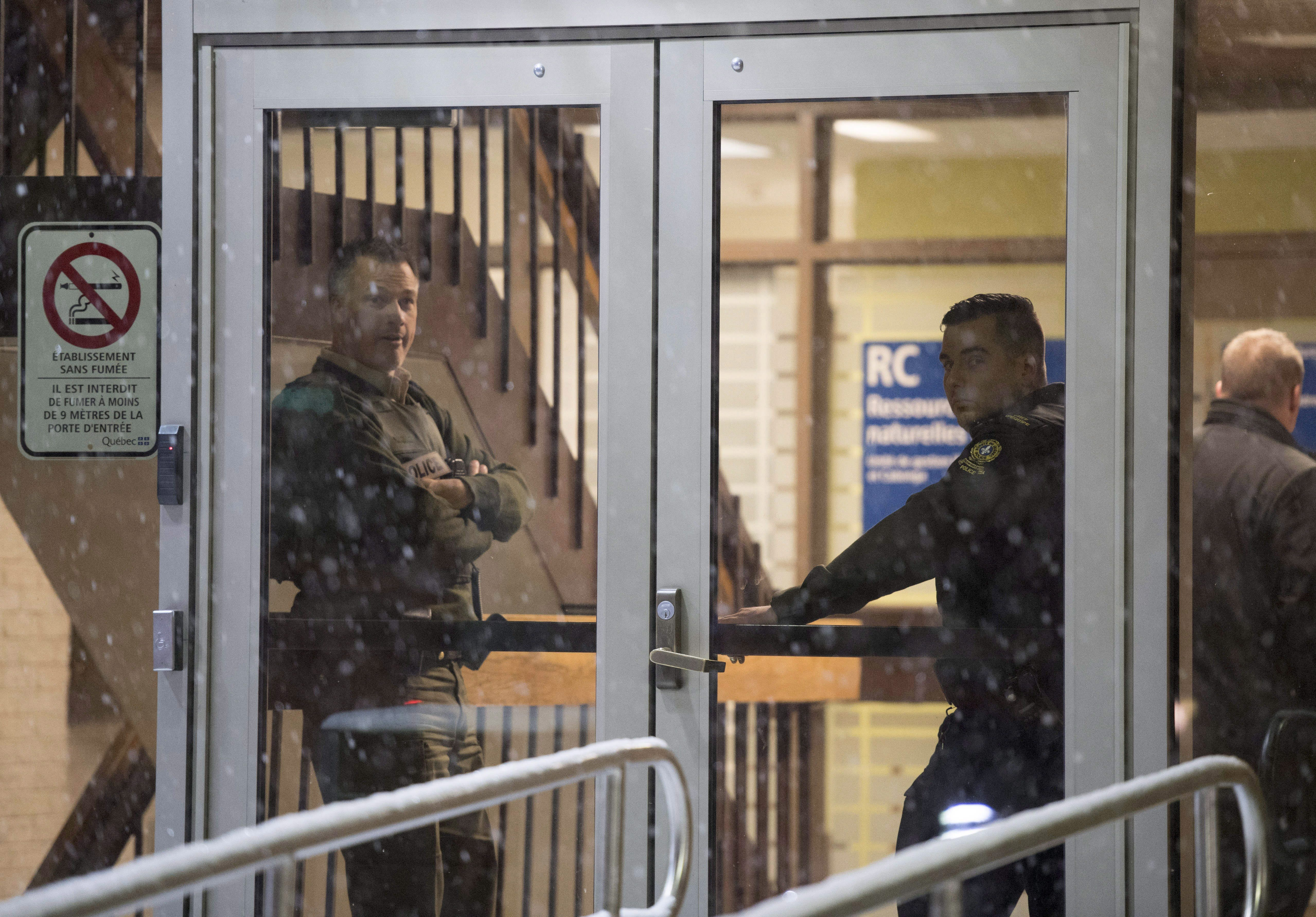 Police stand in the front doors of the courthouse in Maniwaki, Que. after two people were injured in...