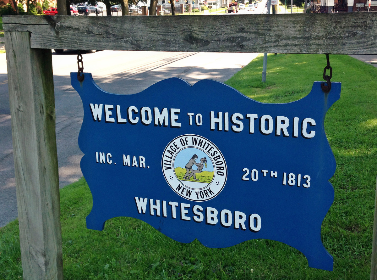 In this photo taken July 16, 2015, a welcome sign on the village green, Whitesboro, N.Y., displays the village seal. Whitesboro will let voters decide whether to keep the longtime village seal that has been called offensive to Native Americans. (Observer-Dispatch via AP)  ROME OUT; MANDATORY CREDIT