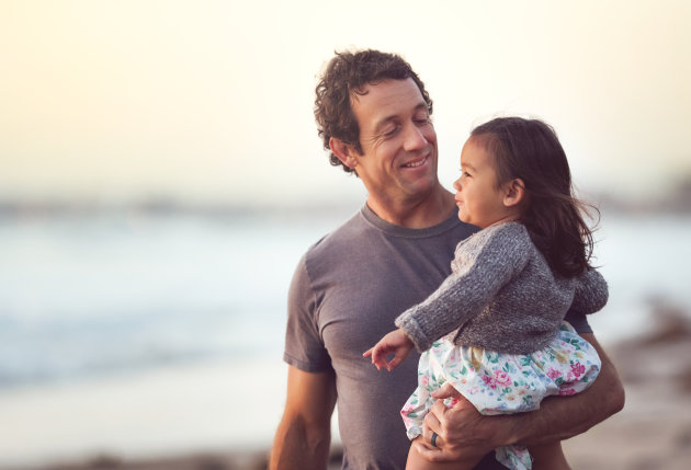 A handsome middle aged dad holds his mixed race daughter during a walk on the