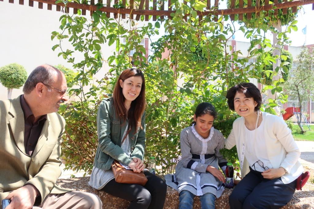 学校の校庭で夢を語るハーラさんを囲んで。左から校長先生、吉田UNRWA渉外・プロジェクト支援担当官、妹尾