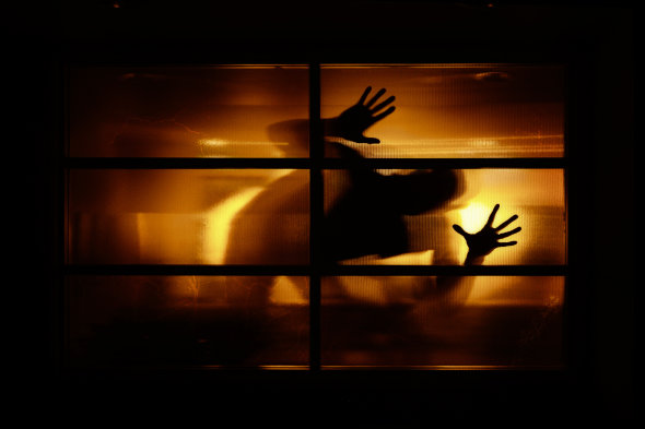 Spooky human form looking through window